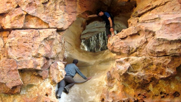 Rock scrambling up the Wolfberg Cracks, South Africa. Ancient red sandstone walls form nature's cathedral, carved high ...