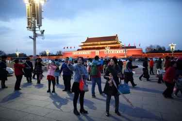 A woman takes a selfie photograph in front of Tiananmen Gate in Beijing, China.