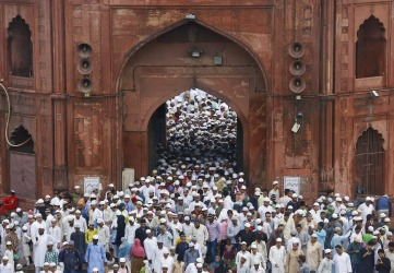 Muslims leave through a gate of the Jama Masjid (Grand Mosque) after offering prayers on the occasion of Eid al-Fitr in ...