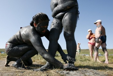 Women smear each other with mineral-rich blue mud on the bank of Tus lake in Khakassia region, southwest of the Siberian city of Krasnoyarsk, Russia. During the summer, Russians from different regions travel to lake Tus, famed for the curative properties of its black and blue sediments, to bathe in the salty water and smear themselves with mud.