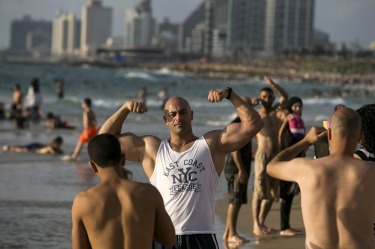 A Palestinian from Bethlehem flexes his muscles on a beach of the Mediterranean in Tel Aviv during Eid al-Fitr, which ...
