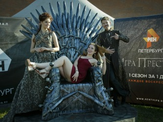 A woman poses for a photo at the throne with actors dressed as persona from a Game of Thrones during a historical ...