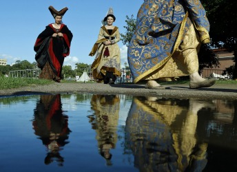 Members of medieval knights historical clubs are reflected in the water as they walk to the venue during a historical ...