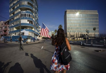A tourist holds a United States' national flag as she walks towards the US embassy, in Havana. A new era began in Cuba ...