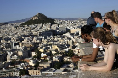 Tourists look at the city skyline from a viewing location on Acropolis Hill in Athens, Greece.