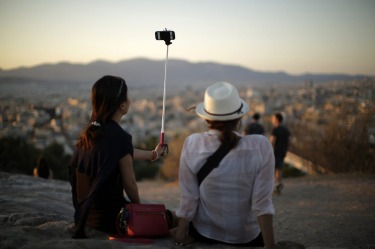 Tourists use a selfie stick to photograph themselves against the backdrop of the Parthenon temple as they watch the sun ...