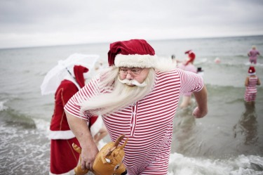 Participants of the World Congress of Santa Clauses 2015 take part in the annual swim at Bellevue beach, north of Copenhagen, Denmark.