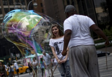 A man circles a tourist in a giant soap bubble at Columbus Circle near Central Park in New York.