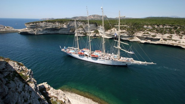 One of Star Clippers' tall ships sails into a cove in Corsica.