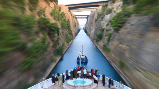 Tourists on the bow of a small cruise ship being pulled by a tug, early morning transit of Corinth Canal, Greece.