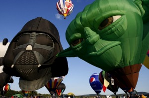 """Hot air balloons shaped as """"Star Wars"""" characters Darth Vader (L) and Yoda (R) are inflated at sunrise on day one of the ..."""