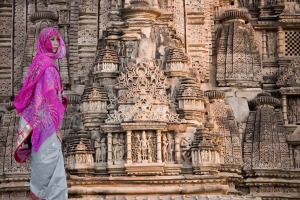 An Indian woman stands next to the carvings on the Khajuraho Temples in Madhya Pradesh, India.