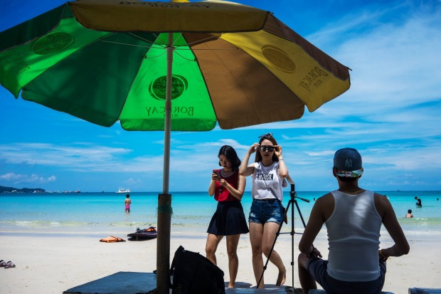 Korean tourists sit and stand below a parasol on White Beach in Boracay, the Philippines. The Philippines is an ...