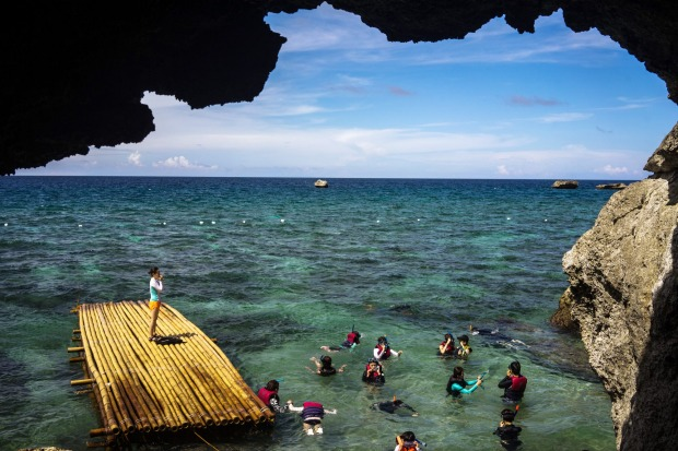 Tourists snorkel next to a raft and caves at the Crystal Cove island in Boracay, the Philippines. The Philippines is an ...