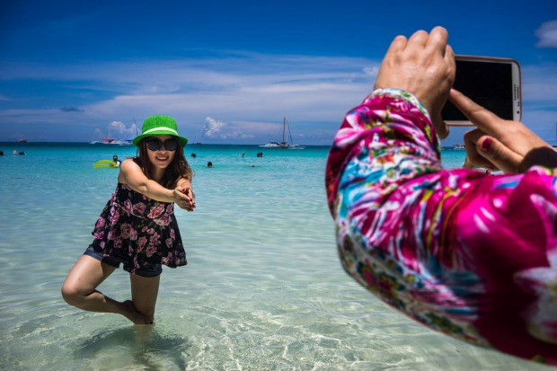 A Chinese tourist poses for a photograph in the sea at White Beach in Boracay, the Philippines. The Philippines is an ...
