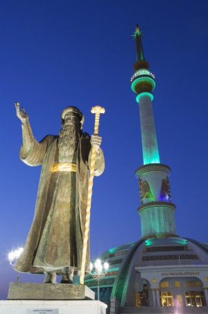 Statue in front of Independence Monument at dusk, Ashgabat, Turkmenistan.