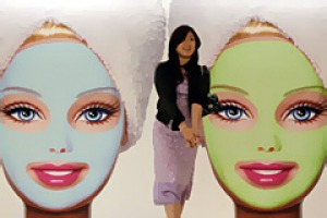 A woman walks past a Barbie doll poster during the opening ceremony of Barbie Shanghai flagship store March 6, 2009.
