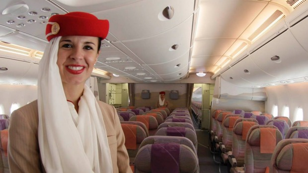 A steward poses at the economy class section of an Emirates aircraft.