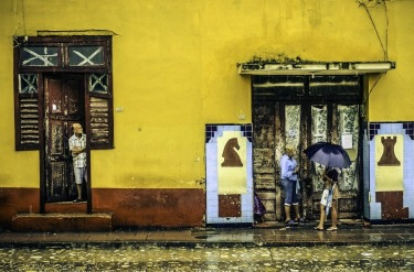 A sudden downpour in Trinidad, Cuba, had locals running for shelter - to the amusement of an elderly resident..This image was shot in June 2015 when we were also caught in the rain!