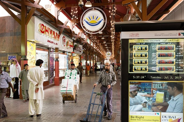 Workers wheel trolleys past a gold price sign board in the Dubai Gold Souk in the Deira district of Dubai.