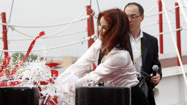 Priscilla Presley smashes a bottle of champagne on the American Queen as she re-christens the refurbished river cruise liner.