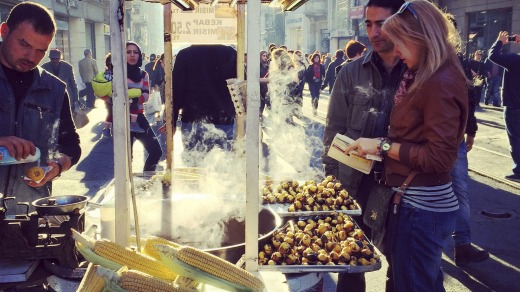 Couple buying grilled corn on the cob on famous Istiklal Avenue, Istanbul.
