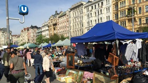 Trestle tables are piled high with household goods, clothes and art at the Vienna flea market.