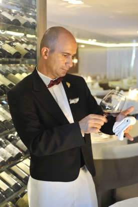 The sommelier prepares wine in the main Deck 2 dining room. Service style is defiantly French.