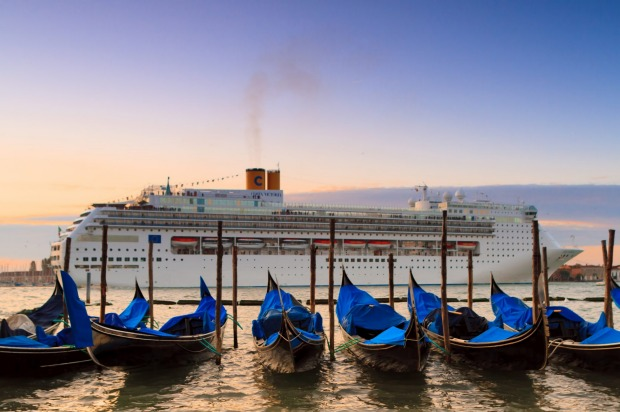 A cruise ship arrives in Venice at sunrise.