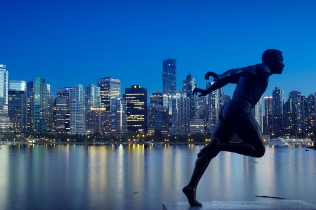 Statue of harry jerome with city in background in Stanley Park, Vancouver.