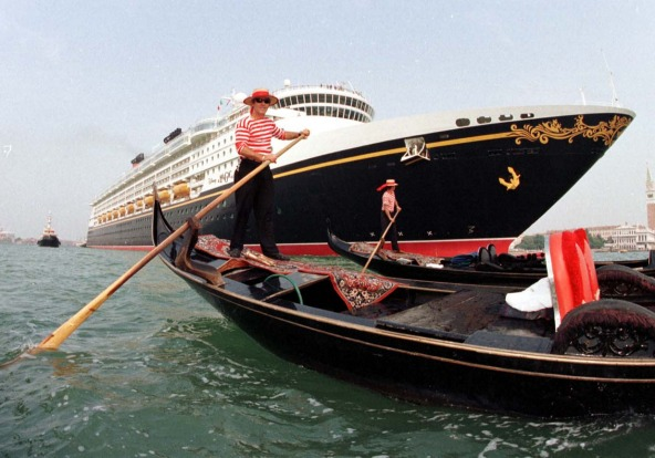 The massive bow of 'Disney Magic' dwarfs the traditional Gondaliers as it departs Venice, Italy.