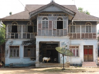 A semi abandoned house in Mrauk U, typical of much of Myanmar, with its faded grandeur, and in this case incongruous ...