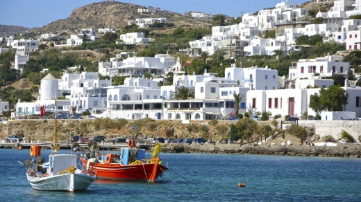 Mykonos' harbour is surrounded by gleaming white houses, resorts and developments.
