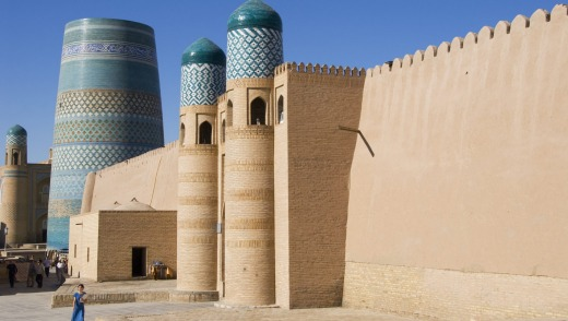 The Kukhana Ark fortress in front of the turquoise-tiled Kalta Minor Minaret in Ichon-Qala in Uzbekistan, Central Asia.
