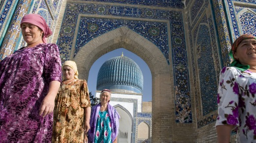 Women in traditional dress leave after paying homage at the Guri Amir, Timur's Mausoleum, in Samarkand, Uzbekistan.