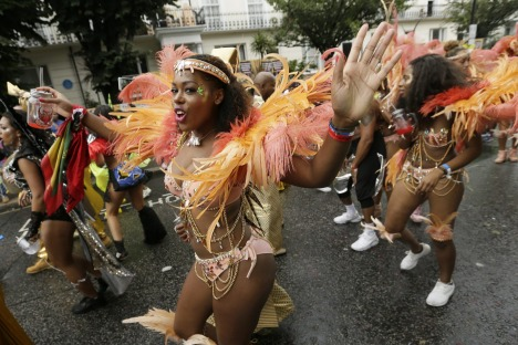A costumed reveller performs in the Notting Hill Carnival in London, Monday, Aug. 31, 2015. Held each August Bank ...