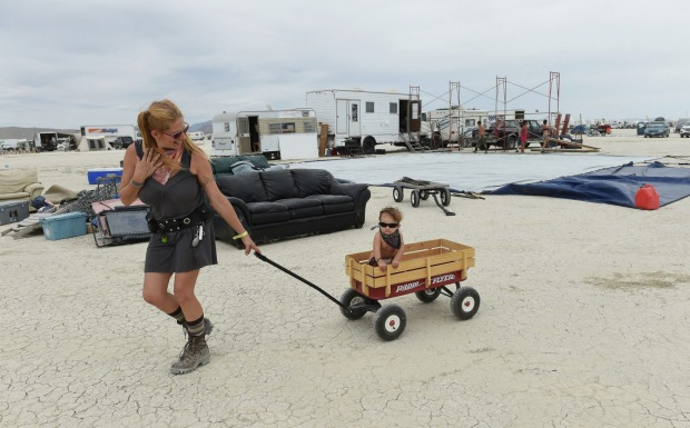 Mima Hall of Sparks pulls her son Makai Hall around in a wagon while their camp is being set up at Burning Man.