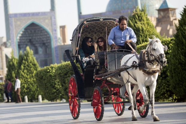 Iranian tourists ride in a horse drawn carriage through Naqsh-e-Jahan square in Isfahan, Iran.