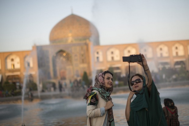 Iranian tourists take a selfie photograph near the water fountains on Naqsh-e-Jahan square in Isfahan, Iran.
