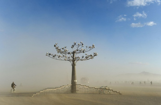 A 'burner' rides next to a sculpture during a dust storm at Burning Man in the Black Rock Desert near Gerlach, Nevada. ...