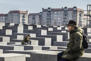 erlin, Germany - March 7, 2015: Middle age man looks out over the Holocaust memorial in central Berlin, Germany. The ...