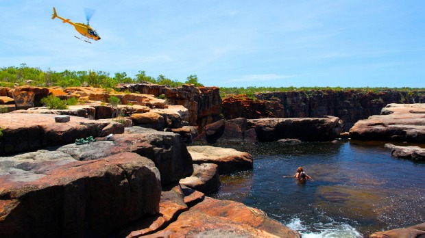 The Great Escape's helicopter dives over the King George Falls as rockpool swimmers look on.