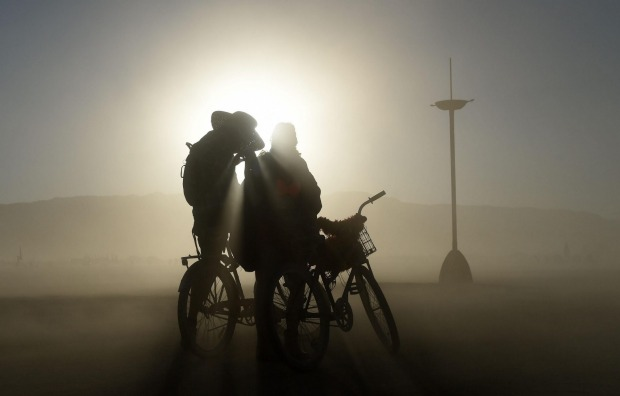 A couple cycling through the playa pauses during a dust storm at Burning Man in the Black Rock Desert near Gerlach, Nevada.