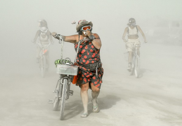 Participants make their way through dust at Burning Man in the Black Rock Desert of Nevada.