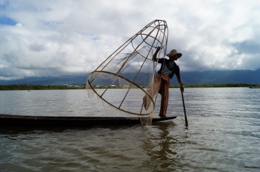 On Inle Lake in Burma the fisherman use distinct way to row their dug out boats. Standing at the stern on one leg while ...