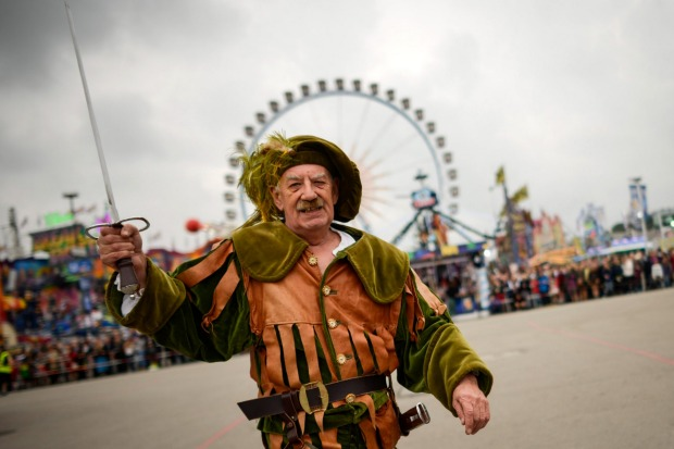 A participant dressed in historical outfit marches in the Parade of Costumes and Riflemen (Trachten- und Schuetzenzug) ...