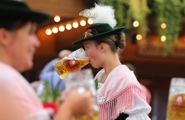 A woman in traditional Bavarian clothes  drinks beer in a beer tent at the 182nd Oktoberfest in Munich, Germany.