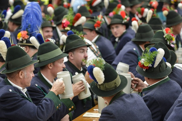 Men in traditional bavarian clothing celebrate at the traditional tent after the Parade of Costumes and Riflemen ...