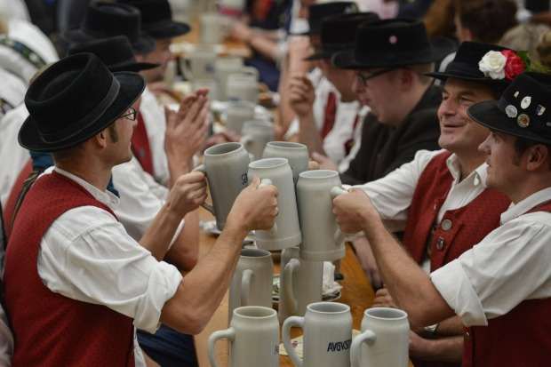 Men in traditional bavarian clothing bring out a toast as they celebrate at the traditional tent after the Parade of ...