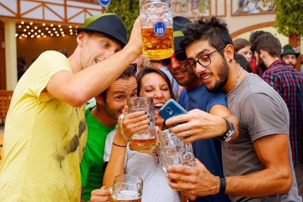 Revelers take photos as they drink beer at Hofbraeuhaus beer tent on the opening day of the 2015 Oktoberfest in Munich, ...